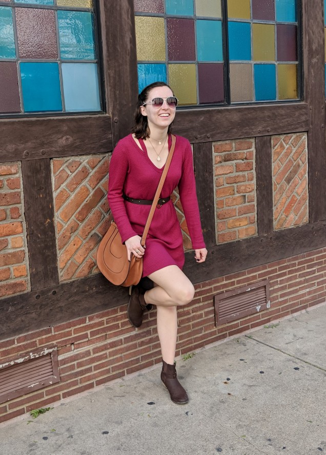 girl laughing in a red dress with brown boots and aviator sunglasses